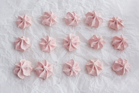 Pink meringues on baking paper sheet photo