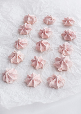 kiss biscuits: Pink meringues on baking paper sheet