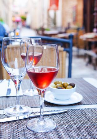 杯在桌上的玫瑰酒红色在夏天街道餐馆