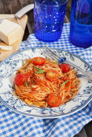 Portion of fresh spaghetti with tomato sauce on wooden table photo