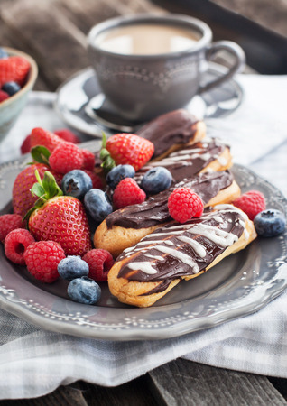 Chocolate eclairs and fresh berries on plate with cup of coffee on the background photo