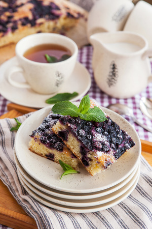 Portion of fresh homemade blueberry cake and cup of tea on the background