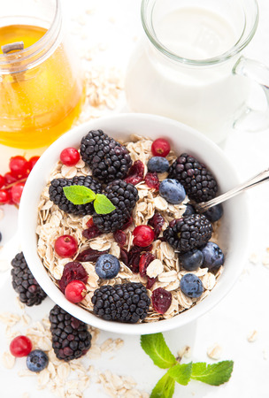 Healthy breakfast with granola and fresh berries on white photo