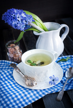 Cup of fresh herbal tea with mint on wooden table photo