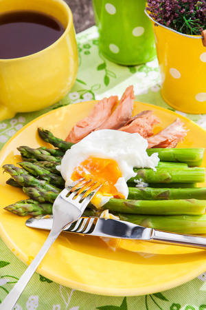 Poached egg and green asparagus for breakfast photo