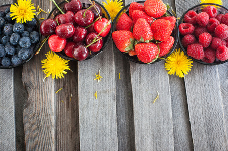 Fresh cherry, strawberry, blueberry and raspberry on wooden table, copy space