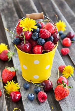 Fresh cherry, strawberry, blueberry and raspberry in a bucket on wooden table Stock Photo