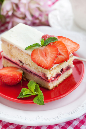 Piece of  strawberry cake with whipped cream and fresh berries