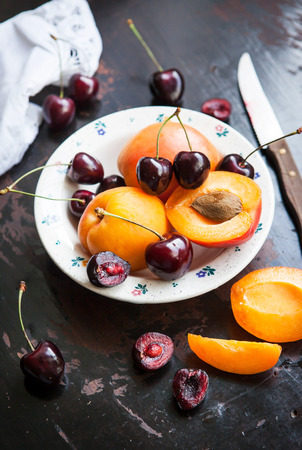 Fresh apricot and cherry in a bowl on wooden table Stock Photo