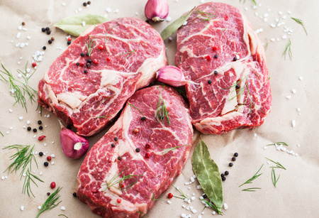 raw: Raw beef ribeye steak on a baking paper, ready to cook Stock Photo