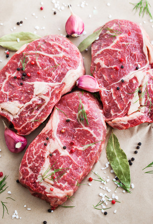 Raw beef ribeye steak on a baking paper, ready to cook Stock Photo