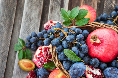 Fresh autumn fruits - pomegranate, plums, grapes and apples Stock Photo