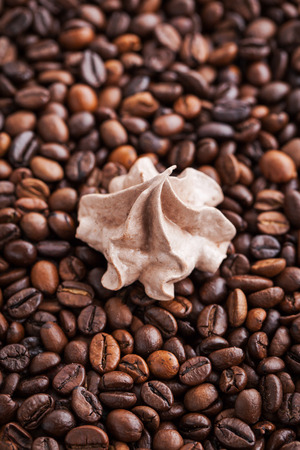 kiss biscuits: Chocolate meringues on coffee beans background