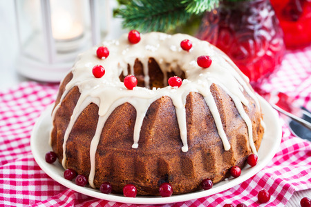 Holiday bundt cake decorated with icing and cranberry