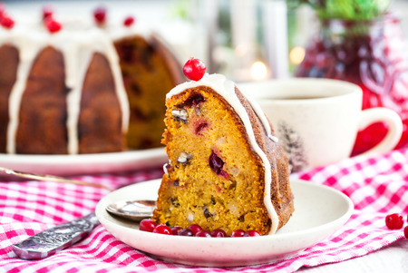 Piece of holiday bundt cake decorated with icing and cranberr Stock Photo