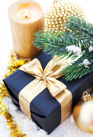 Golden Christmas composition with gift box, candle and branch of spruce photo