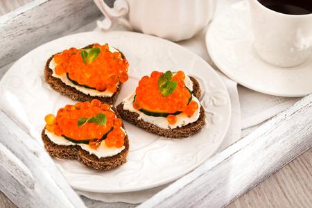 petit dejeuner romantique: Petit-d�jeuner romantique avec cardiaques toasts forme avec du caviar rouge et le caf� - notion Valentine