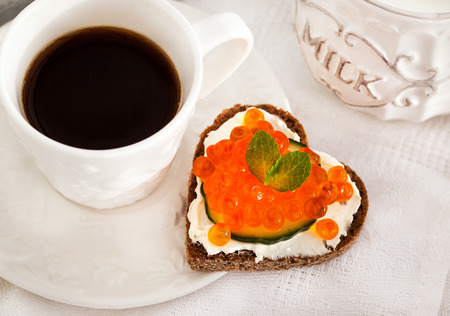 Romantic breakfast with heart shaped toasts  with red caviar and coffee - Valentine concept photo