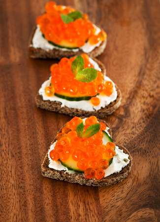 Heart shaped toasts appetizer with red caviar photo