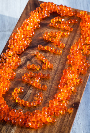 caviar: The word Caviar made from red caviar on wooden board Stock Photo