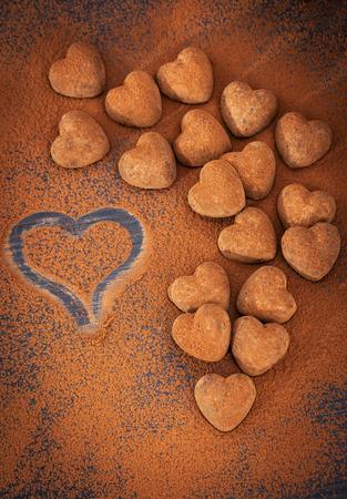 cafe bombon: En forma de coraz�n de trufas de chocolate en la mesa de polvo de cacao, el concepto de Valentine Foto de archivo