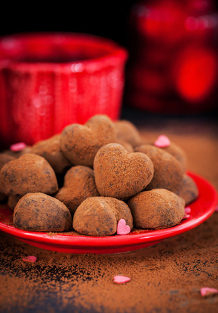 cafe bombon: En forma de coraz�n de trufas de chocolate en la placa roja, concepto de San Valent�n Foto de archivo