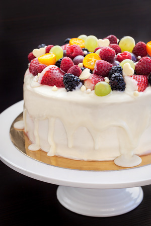 white cream: Homemade white chocolate frosted cake decorated with fresh berries and fruits
