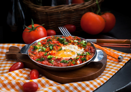 Shakshuka - fried eggs with tomatoes, onion, pepper and spices in iron pan, dark style