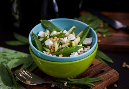 Fresh delicious cucumber, pods green peas, feta and pine nuts salad, dark style photo