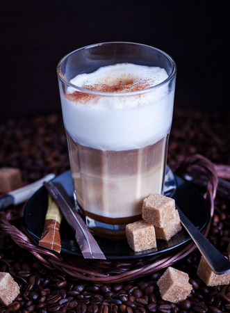 Glass of fresh hot tasty latte macchiato on coffee beans and sugar background, dark style photo