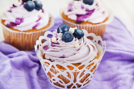 Tasty blueberry cupcakes decorated with cream and fresh berries Archivio Fotografico