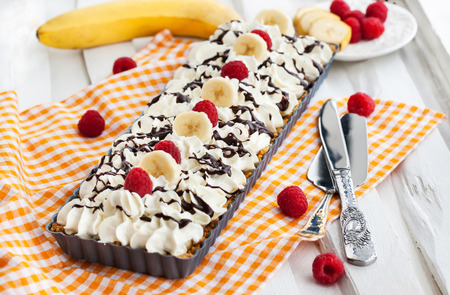 Banoffee pie (banana and toffee) decorated with whipped cream, fresh banana and raspberry