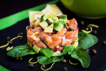 Tasty salmon and avocado tartar, dark background Stock Photo