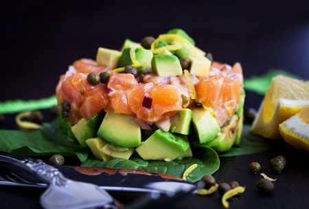 Tasty salmon and avocado tartar, dark background Stock Photo