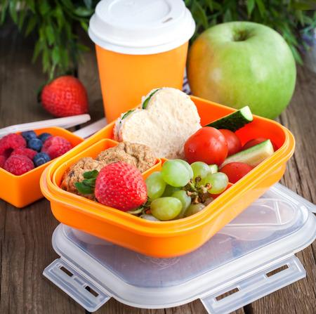niños comiendo: Caja de almuerzo para los niños con sándwich, galletas, verduras y frutas frescas