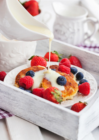Cheese pancakes (syrniki) with fresh strawberry, raspberry,  blueberry and coffee on the tray