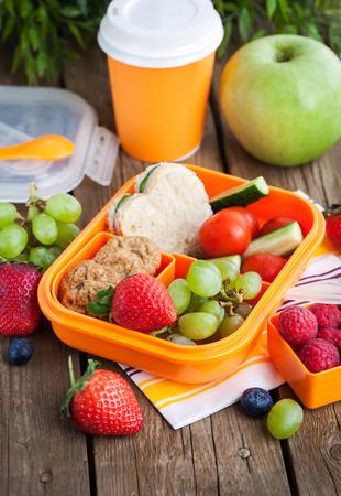 envases de plástico: Caja de almuerzo para los niños con sándwich, galletas, verduras y frutas frescas
