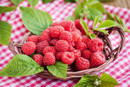 gamme de produit: Fresh organic ripe raspberry with leaf in basket,  selective focus