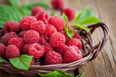 Fresh organic ripe raspberry with leaf in basket,  selective focus
