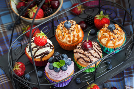 fruit cake: Set of different delicious cupcakes on dark