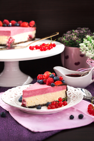 cheese cake: Portion of delicious raspberry cheesecake decorated with fresh berries and chocolate, on dark