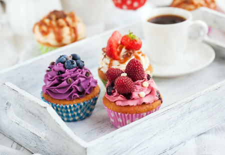 Different delicious cupcakes and coffee cup on white wooden tray 스톡 콘텐츠