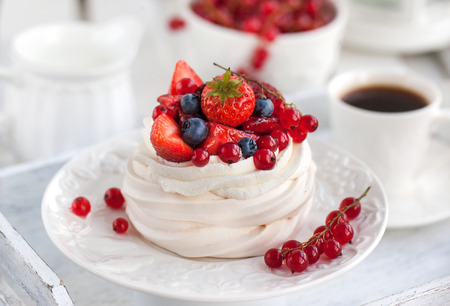 Pavlova meringue cake with fresh berries on white background
