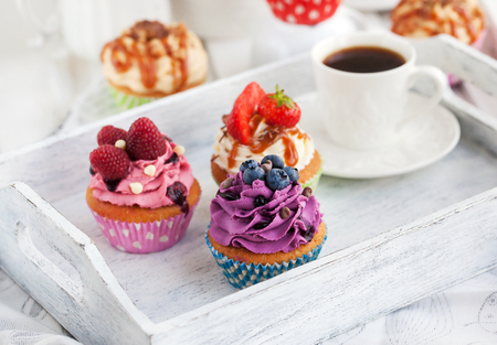 Different delicious cupcakes and coffee cup on white wooden tray Stock Photo