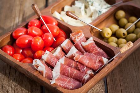 queso: delicioso aperitivo en la placa de madera - jam�n, queso, aceitunas y tomate cherry
