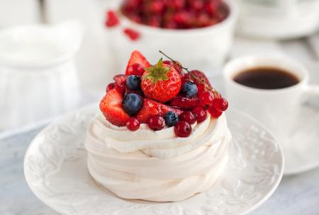 Pavlova meringue cake with fresh berries on white background