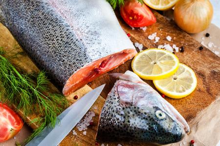 redfish: Process of cutting raw salmon on a board