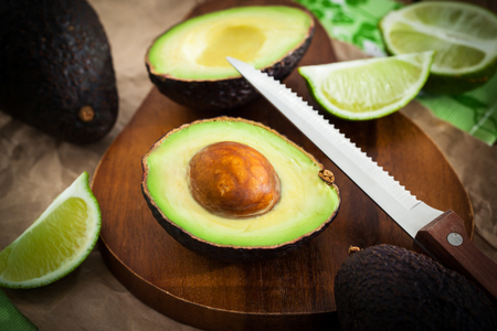 Sliced fresh avocado and lemon lime on cutting board, on wooden background
