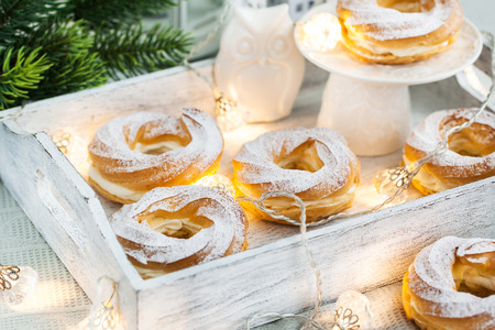 choux: Cream puff rings (choux pastry) on white christmas background