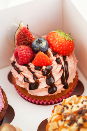 Delicious cupcake decorated with fig, strawberry and raspberry